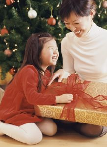 Mother and Daughter Sitting by a Christmas Tree With a Christmas Present