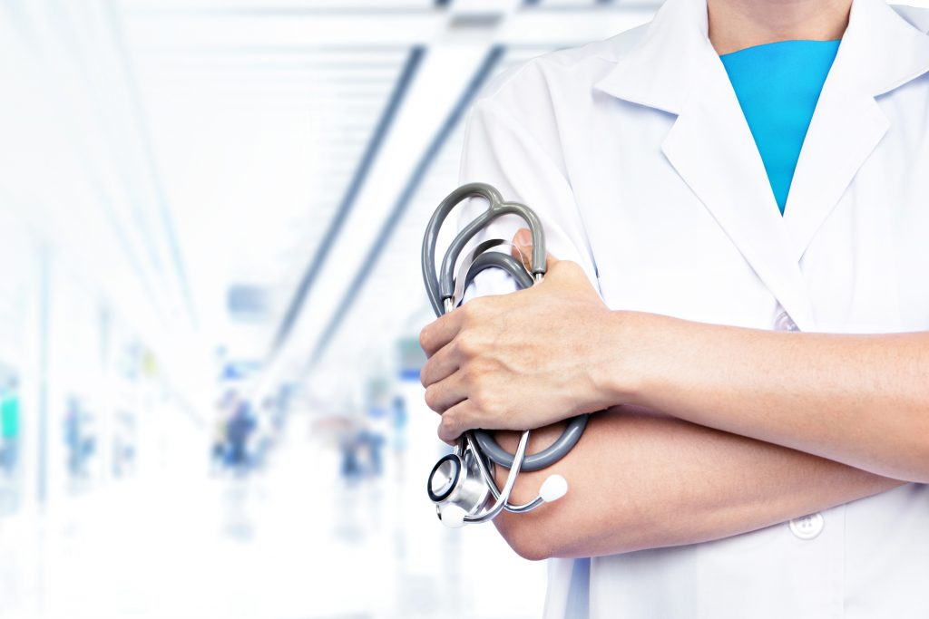 Doctor with stethoscope on blurred hospital background.